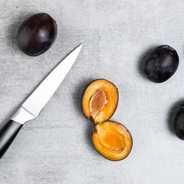 Close-up shot of plums and knife on wooden table Free Photo