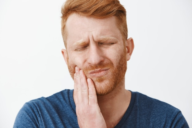 Close-up shot of redhead man with beard feeling pain in teeth, frowning and making suffering expression with closed eyes, touching cheek, having need to call dentist for curing decay or rotten tooth Free Photo