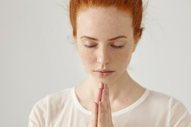 Close up shot of religious young ginger woman in white blouse meditating or praying keeping eyes closed and hands pressed together, hoping for the best. people, religion, spirituality, prayer Free Photo