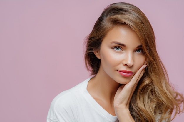Close up shot of self confident beautiful caucasian woman has long hair combed on one side Premium Photo