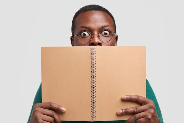 Immagine ravvicinata di uomo nero scioccato copre il viso con blocco note a spirale, si sente stupito, modelli su sfondo bianco studio, legge note scritte in notebook Foto Gratuite