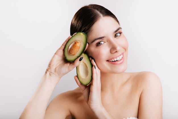 Close-up shot of smiling green-eyed woman without makeup on white wall. model demonstrates avocado skin benefits. Free Photo