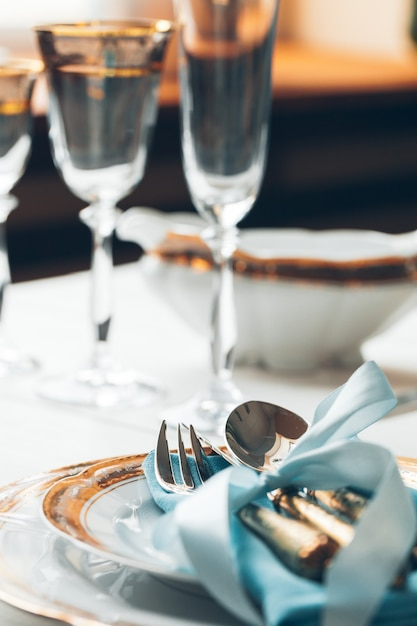 Close up shot of table setting for fine dining with cutlery and glassware Premium Photo