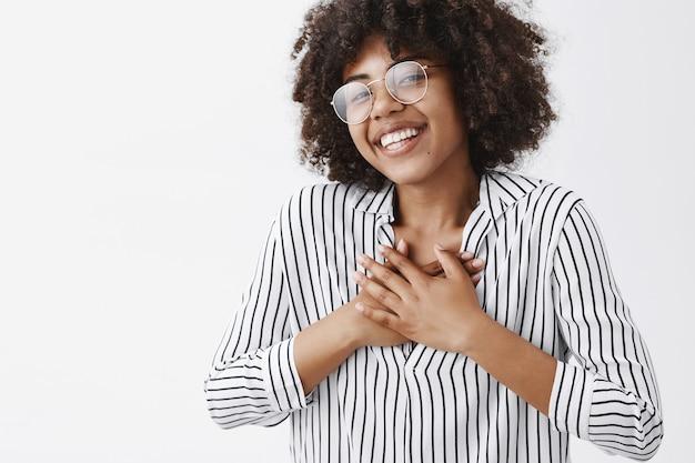 Inquadratura ravvicinata della ragazza dalla carnagione scura felice e toccata con l'acconciatura afro in occhiali e camicetta a righe che tengono le mani sul petto e sorridono ampiamente soddisfatti di ricevere i complimenti Foto Gratuite