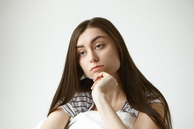 Immagine ravvicinata di infelice bella giovane donna europea bruna ventenne che tocca il mento, con espressione facciale indifferente, sentirsi annoiato, trascorrere il fine settimana a casa, non fare nulla Foto Gratuite