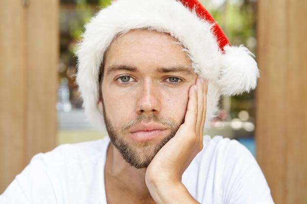 Immagine ravvicinata di sconvolto giovane hipster uomo con stoppie che indossa un cappello rosso con pelliccia bianca tenendo la mano sulla sua guancia, sentendosi solo e annoiato Foto Gratuite