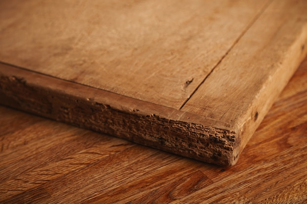 Close up shot of a very old and battered chopping board with deep cuts, pieces missing lying on a rustic wooden table Free Photo