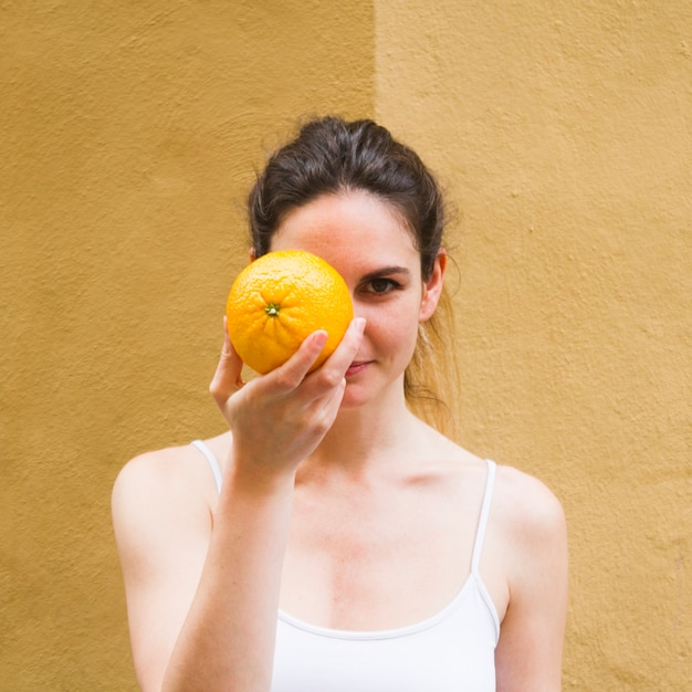 Close up shot woman covering face with orange Free Photo