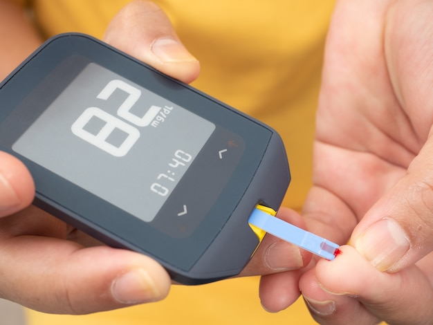 Close up shot of woman's hands making blood sugar level test Premium Photo