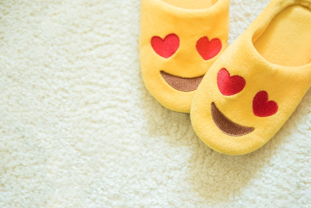 Close-up shot yellow plush house slippers made as the smiling emoji with heart eyes on white carpet Premium Photo