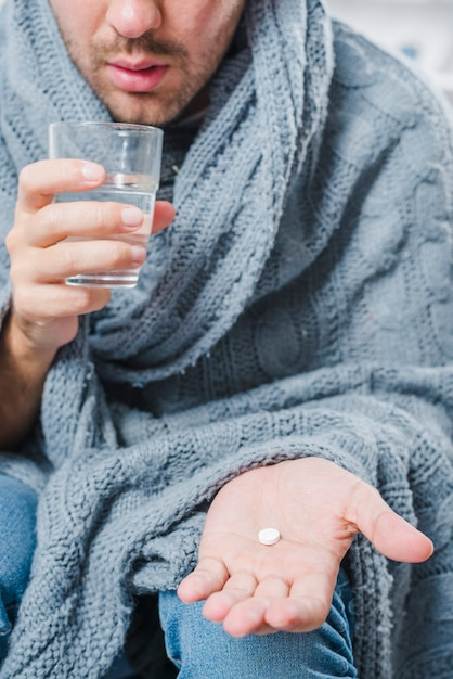 Close-up of a sick man showing white pill in his hand and holding water glass Free Photo