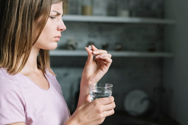 Close-up of a sick young woman with pill and glass of water Free Photo