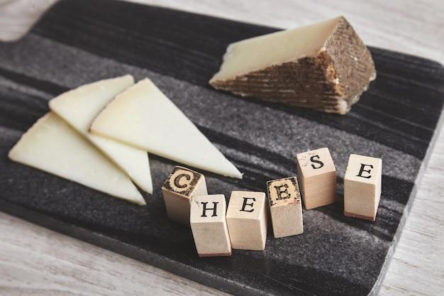 Close up lato focalizzato lettere formaggio avanti formaggio di capra unfocused sul bordo di pietra di marmo isolato su tavola di legno vuota Foto Gratuite
