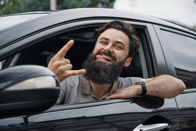 Close up side portrait of happy man driving car Free Photo