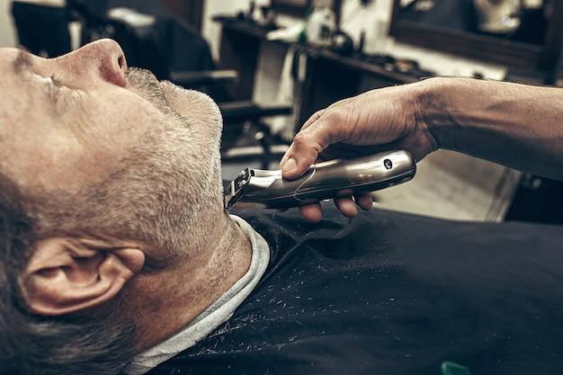 モダンな理髪店でひげの手入れをしているハンサムなシニアのひげを生やした白人男性のクローズアップ側縦断ビューの肖像画。 無料写真