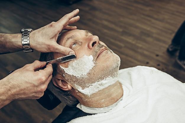 クローズアップ側トップビューハンサムなシニアのひげを生やした白人男性ひげグルーミング現代の理髪店で。ストレートかみそりを使ってひげの散髪をする美容師。理髪店のコンセプトです。 無料写真