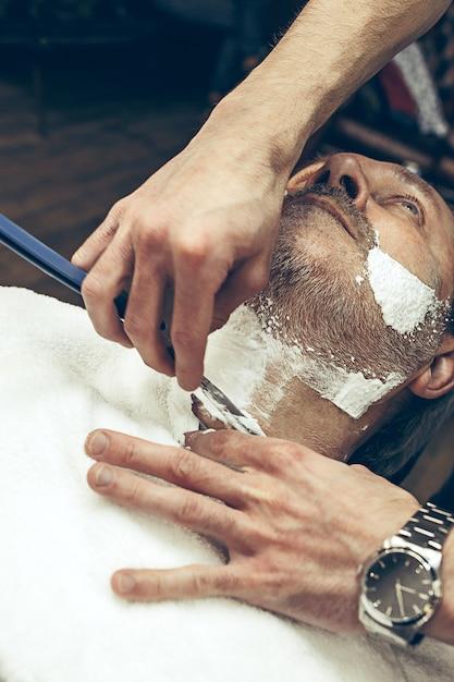 クローズアップ側トップビューハンサムなシニアのひげを生やした白人男性ひげグルーミング現代の理髪店で。 無料写真