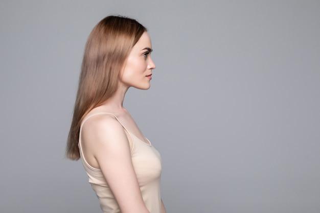 Закройте вверх по взгляду со стороны молодой женщины стоя изолированная серая стена Бесплатные Фотографии