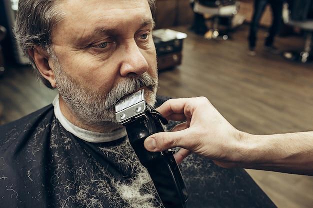 モダンな理髪店でひげのグルーミングを取得するハンサムなシニアのひげを生やした白人男性のクローズアップ側ビューの肖像画。 無料写真