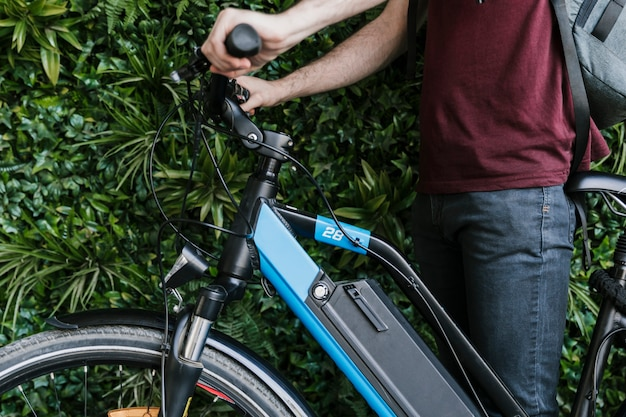 Close up sideways cyclist holding e-bike with green wall background Free Photo