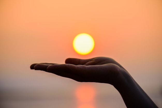 Close up and silhouette of hand holding sun. sun on woman hand. Premium Photo