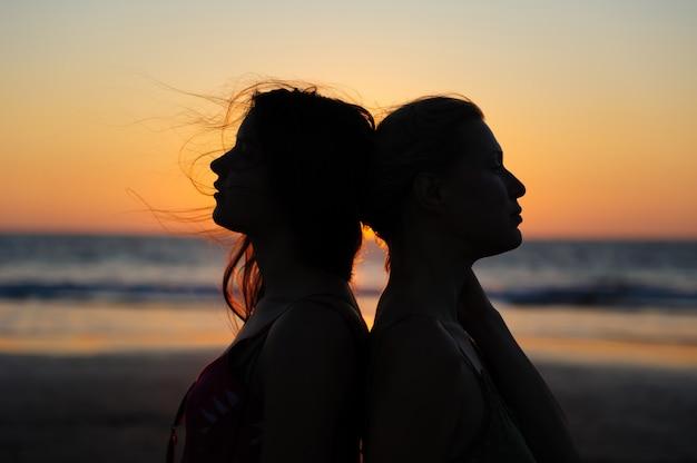 海に沈む夕日のロマンチックなシーンで女性のカップルのシルエットを閉じます。愛の美しい女性の若いレズビアンのカップル。 Premium写真