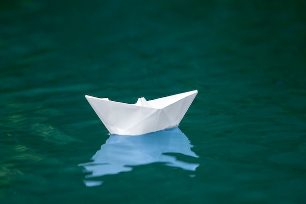 Close-up of simple small white origami paper boat floating quietly in blue clear river or sea water under bright summer sky. freedom, dreams and fantasies concept, copyspace scene. Premium Photo