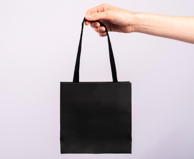 Close-up single black bag held Free Photo