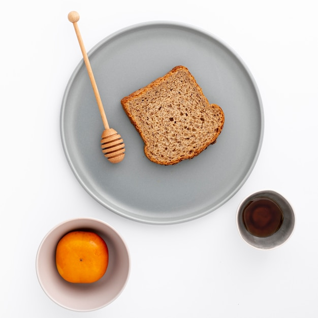 Close-up slice of bread on plate with honey Free Photo