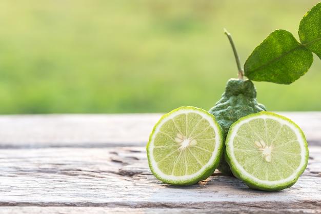 Close up slice green fresh bergamot fruit on wooden table background Premium Photo