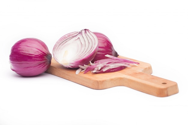 Close up of sliced red onion and whole red onion on a wooden table. Free Photo