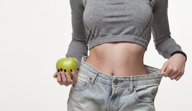 Close-up of slim waist of young woman in big jeans showing successful weight loss Premium Photo