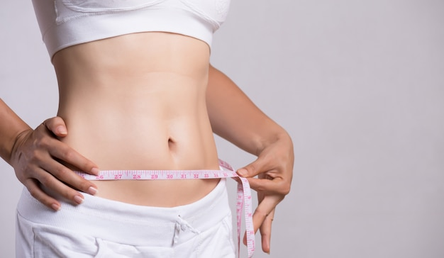 Close up slim young woman measuring her thin waist with a tape measure Premium Photo