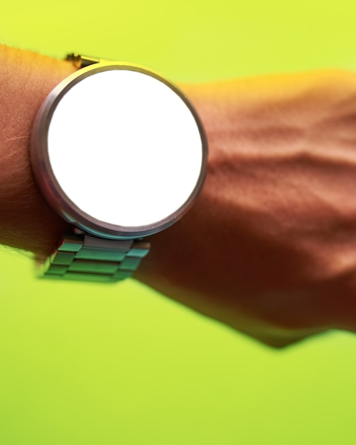 Close up smart watch on hand on bright lime green background with isolated, blank screen f Premium Photo