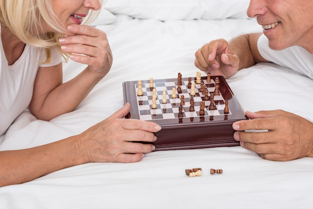 Close-up smiley couple playing chess Free Photo