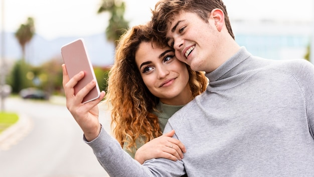 Close-up smiley couple taking selfie outdoors Free Photo