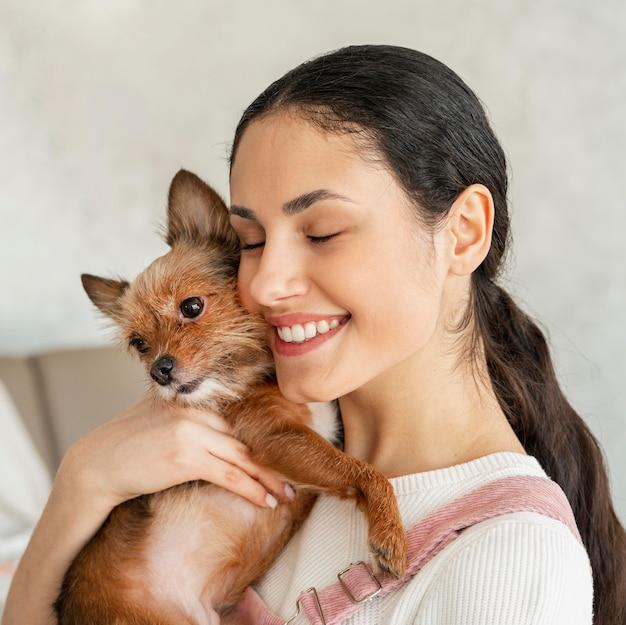 Ragazza di smiley del primo piano che abbraccia l'animale domestico Foto Gratuite