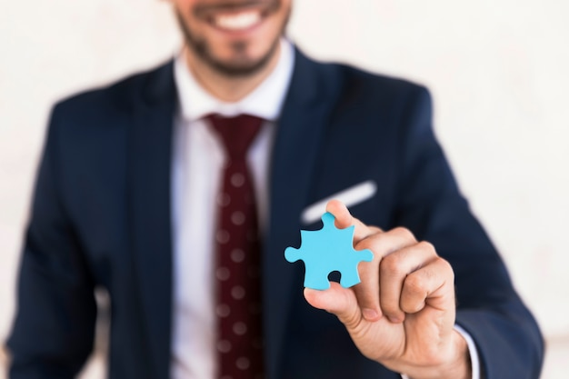 Close-up smiley man holding a puzzle piece Free Photo