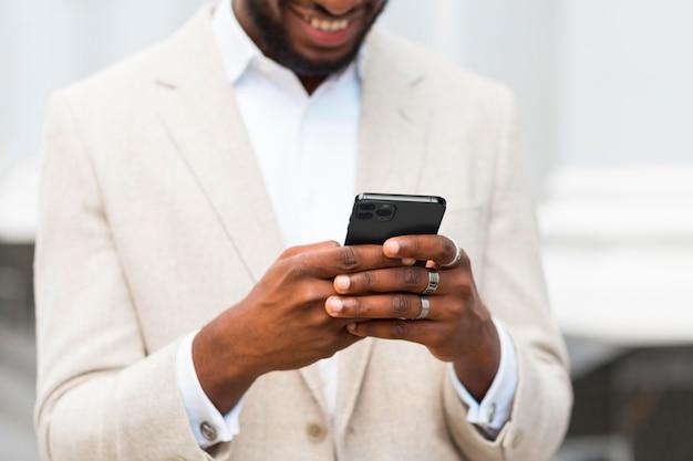 Uomo di smiley del primo piano che tiene smartphone Foto Gratuite