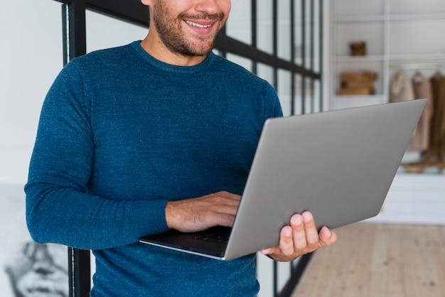 Close-up smiley man using laptop Free Photo