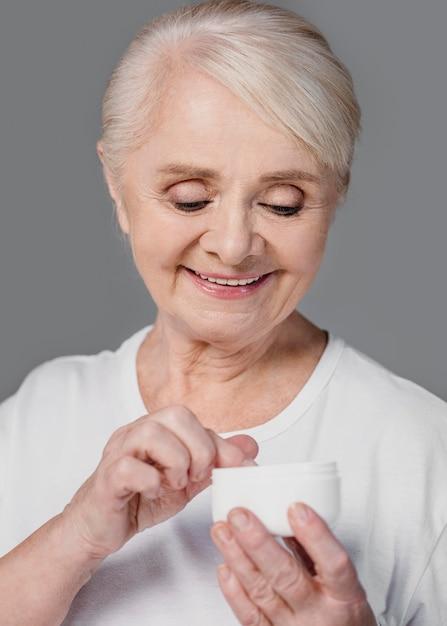 Close-up smiley donna che tiene il contenitore crema Foto Gratuite