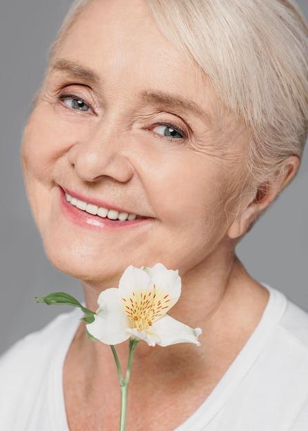 Fiore della holding della donna di smiley del primo piano Foto Gratuite