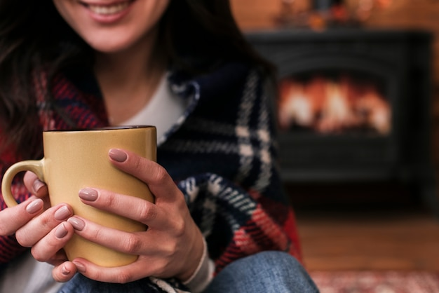 Close-up smiley woman holding hot drink Free Photo