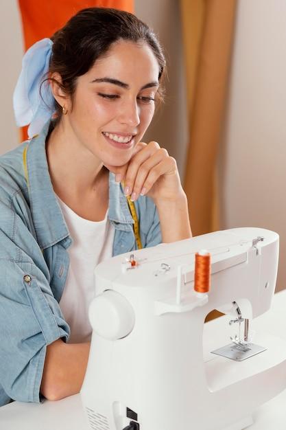 ミシンを見ているクローズアップの笑顔の女性 Premium写真