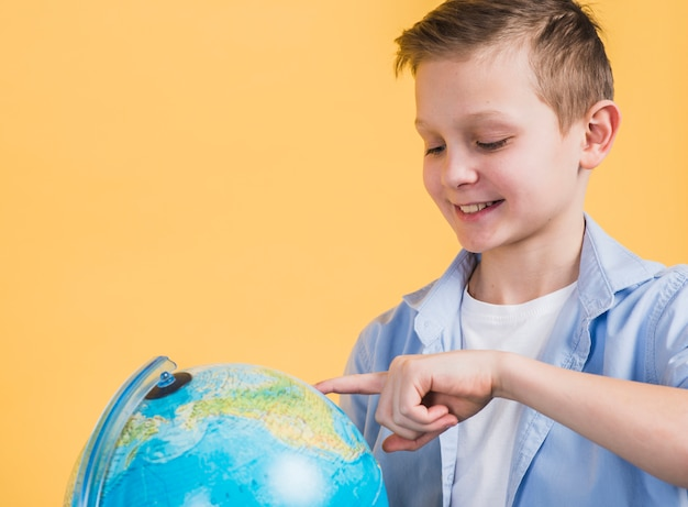 Close-up of smiling boy touching the globe with finger against yellow background Free Photo