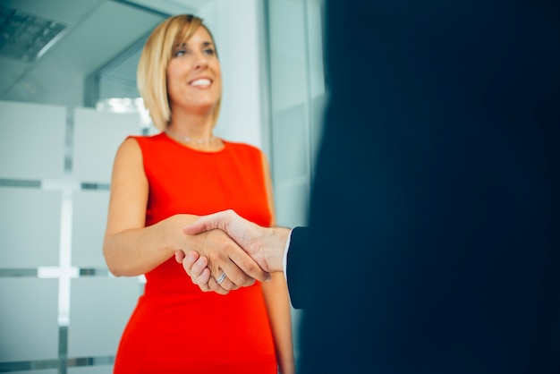 Close-up of smiling businesswoman giving an handshake Free Photo