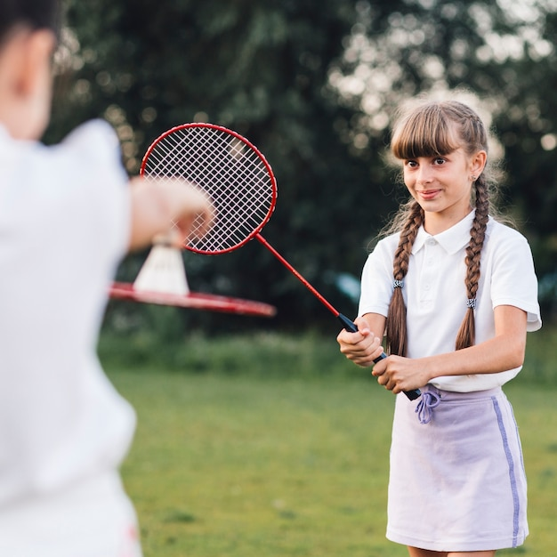 Close-up of a smiling girl playing badminton with her friend Free Photo