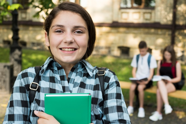 Close up of smiling highschool girl holding book in hands Free Photo