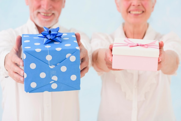 Close-up of smiling husband and wife giving birthday gift box Free Photo
