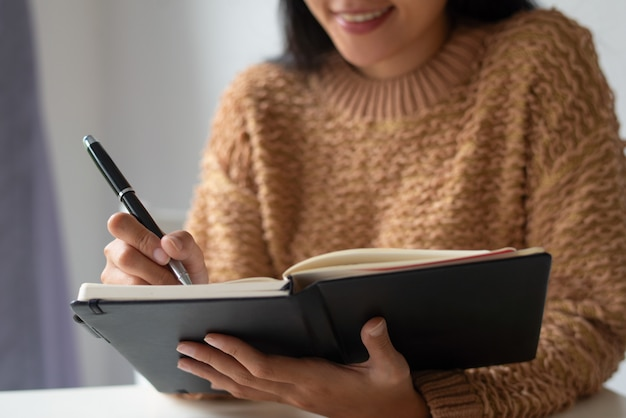 Close-up of smiling lady making notes about ideas in diary Free Photo